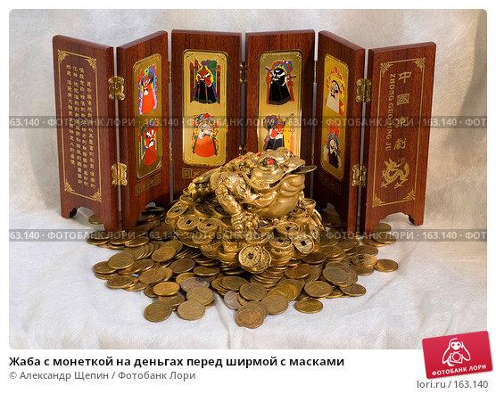 Жаба с монеткой на деньгах перед ширмой с масками, эксклюзивное фото № 163140, снято 29 декабря 2007 г. (c) Александр Щепин / Фотобанк Лори