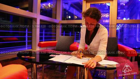 Женщина держит ручку и читает документы, сидя за столом в зале, видеоролик № 3784828, снято 21 июня 2012 г. (c) Losevsky Pavel / Фотобанк Лори
