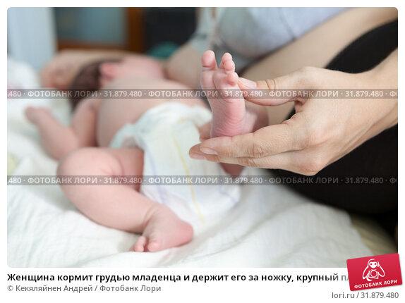 Женщина кормит грудью младенца и держит его за ножку, крупный план. Стоковое фото, фотограф Кекяляйнен Андрей / Фотобанк Лори
