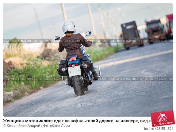 Купить «Женщина-мотоциклист едет по асфальтовой дороге на чоппере, вид сзади», фото № 26551524, снято 14 июня 2017 г. (c) Кекяляйнен Андрей / Фотобанк Лори