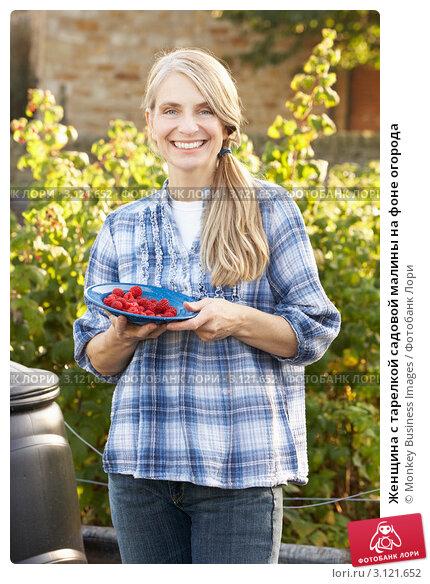 Купить «Женщина с тарелкой садовой малины на фоне огорода», фото № 3121652, снято 12 октября 2010 г. (c) Monkey Business Images / Фотобанк Лори