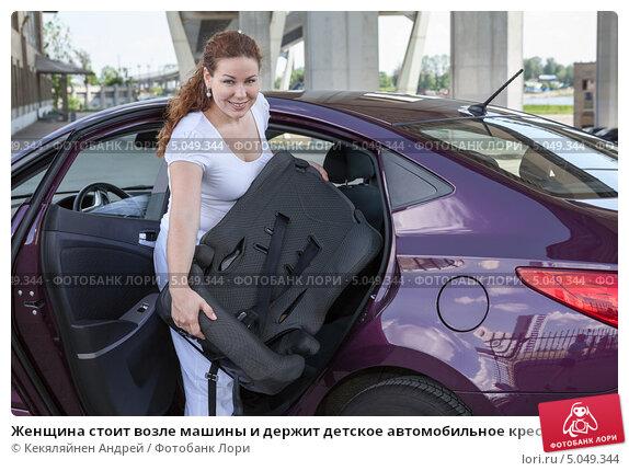 Женщина стоит возле машины и держит детское автомобильное кресло. Стоковое фото, фотограф Кекяляйнен Андрей / Фотобанк Лори